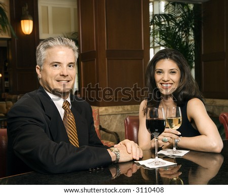 Prime adult Hispanic female and Caucasian prime adult male sitting at bar looking at viewer smiling. - stock photo