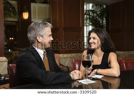 Prime adult Hispanic female and Caucasian prime adult male sitting at bar talking. - stock photo