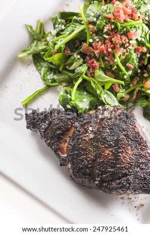 Prime rib eye steak served with spinach sauteed in olive oil with garlic and bacon bits - stock photo