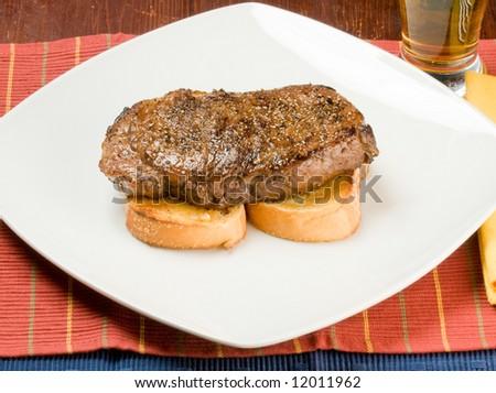 Prime Rib steak on garlic toast, with Blue Cheese and rosemary stuffed potato, mushrooms in balsamic vinegar reduction, with horseradish sauce and beer. - stock photo