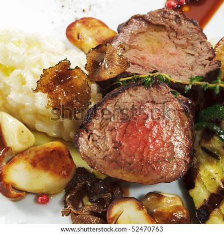 Prime Veal with Risotto, Tartufo Nero (Black Truffle), Zucchini Grill, Porcini and Dried Tomato - stock photo