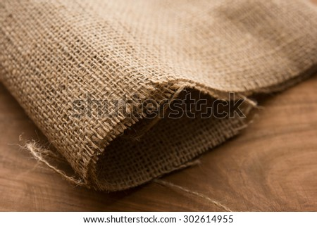 Primitive hemp cloth on rustic wooden table. Shallow depth of field. - stock photo