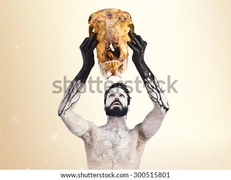 Primitive man offering veal skull over ocher background - stock photo