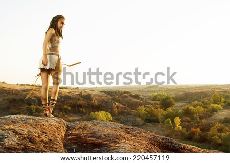 Primitive woman  holding a bow. Amazon woman - stock photo