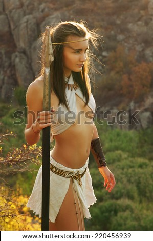 Primitive woman  holding a spear. Amazon woman - stock photo