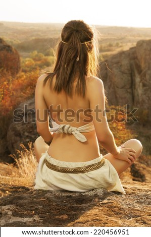Primitive woman sitting on a rock at the sunset. Amazon woman - stock photo