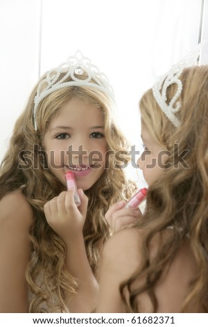 princess little girl painting makeup lipstick on the mirror - stock photo