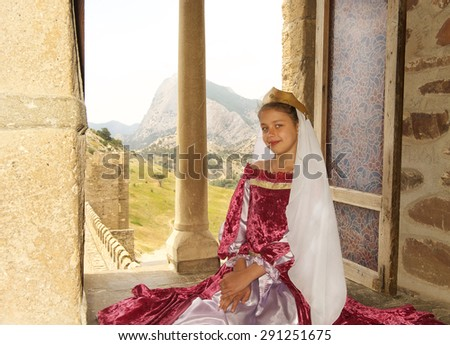 Princess sitting by the window in the castle. Waiting for the prince - stock photo