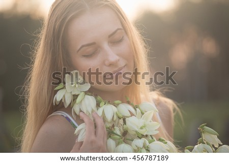 Princess. Young beautiful pretty woman posing in long evening luxury dress against bushes with white flowers. warm evening sun rays