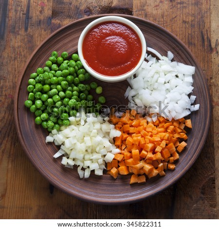 Principal Vegetables and Tomato Sauce cook vegetable sauce Carrot, Celery, Onion, Green Peas. On wooden table - stock photo