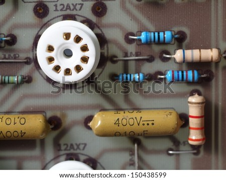 print circuit board of a tube radio amplifier, preamplifier close-up of a tube socket on a circuit board surrounding with capacitors and resistors