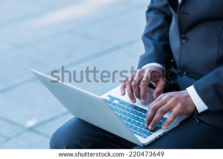 print hands. African man businessman holding a laptop on his knees and looking at the laptop while sitting outdoors in formalwear and hands typing on the keyboard - stock photo