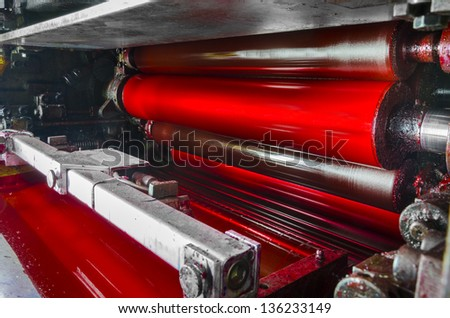 print machine printing press rollers, red magenda color drum, dramatic light - stock photo