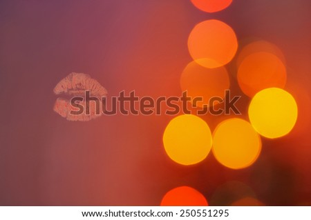 Print of red lips on evening bokeh blurred background - stock photo