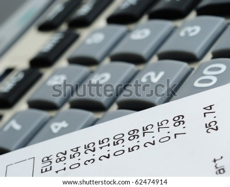 Printed receipt from shop on calculator closeup image - stock photo