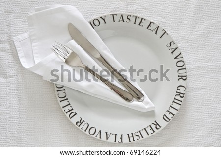 Printed White China plate with serviette and cutlery - stock photo
