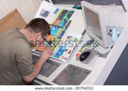 Printer checking a print run at table - stock photo
