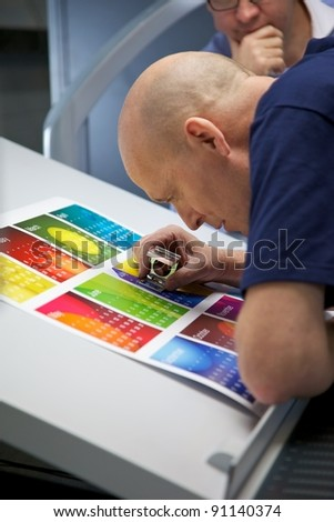 Printer looking through an eye glass to check the registration on a printed calendar - stock photo