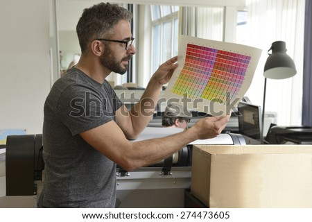 Printing industry: Graphic designer checks the color with color swatch. - stock photo