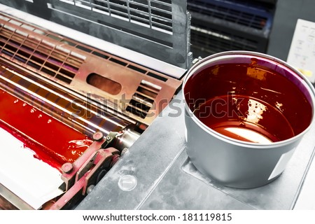printing machine detail and printing ink pot with red color - stock photo