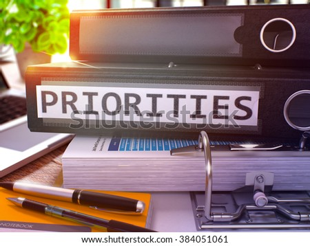 Priorities - Black Office Folder on Background of Working Table with Stationery and Laptop. Priorities Business Concept on Blurred Background. Priorities Toned Image. 3D. - stock photo