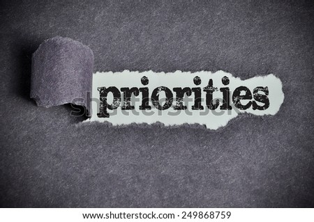 priorities word under torn black sugar paper  - stock photo