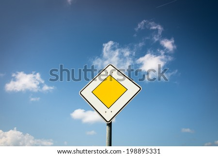 priority road sign (3) with blue sky and clouds - stock photo