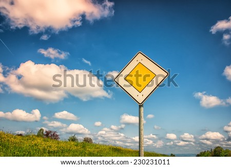 priority road sign with blue sky and clouds - stock photo
