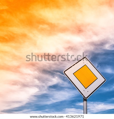 priority road traffic sign with sky and clouds - stock photo