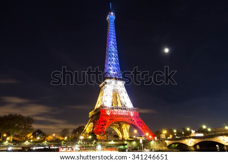 Pris, France-November 18, 2015 : The Eiffel tower lit up with the colors Of the French national flag to honor the victims of November 13 Friday's terrorist attacks in Paris. - stock photo
