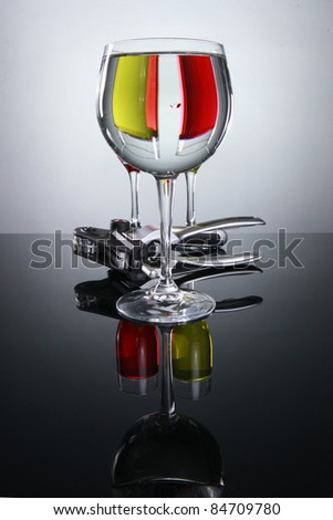 Prismatic view of red wine, white wine, and a corkscrew - stock photo
