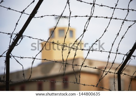 Prison - barbed wire in front of the guard tower - selective focus - stock photo