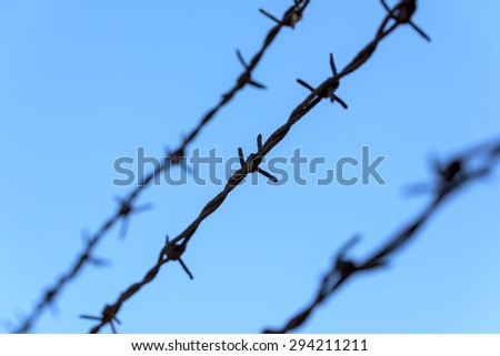 Prison Rusty Barbed Wire On Blue Sky