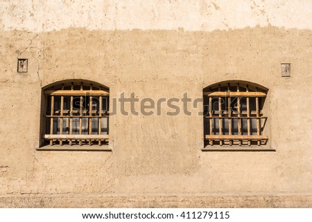 Prison with bars on the windows on a wall - stock photo