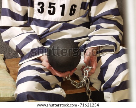Prisoner at cell holding a weight ball. - stock photo