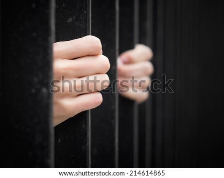 Prisoner behind jail bars - stock photo