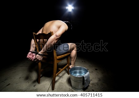 Prisoner being punished with cruel interrogation technique of waterboarding.  The man is restrained and tortured.