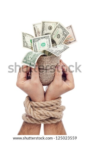 Prisoner of profit - man holding bag of money with hands tied up - stock photo