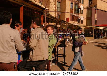 PRISTINA, KOSOVO - JAN 26: A young boy sells cigarettes to crowds of mostly out-of-work young men at a cafe in Pristina, Kosovo, on Saturday, January, 26, 2008.