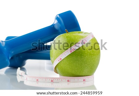 Pristine green apple, two dumbbells, measuring tape isolated on white with reflection. Plenty of copy space. - stock photo
