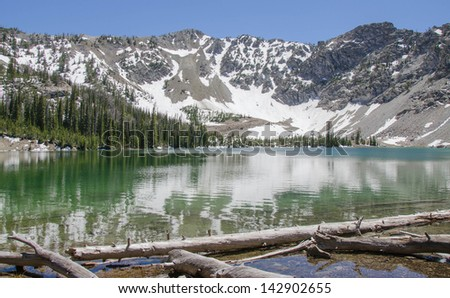Pristine Idaho mountain lake in the Sawtooth National Forest with trees and snow covered peaks in the background reflected upon calm water. - stock photo