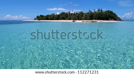 Pristine island with lush vegetation, white sandy beach and a lagoon with turquoise water - stock photo