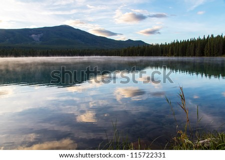 Pristine Lake with some morning fog and cloud reflection - stock photo