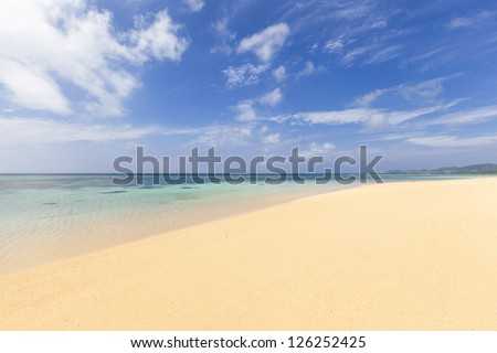 Pristine sandy beach and clear turquoise waters on a sunny, calm day. Sunset beach on Ishigaki Island, Okinawa prefecture, Japan. - stock photo