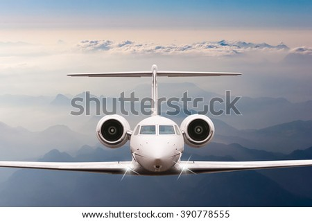 Private Airplane fly over clouds and Alps mountain on sunset. Front view of a big passenger or cargo aircraft, business jet, airline. Transportation, travel concept - stock photo