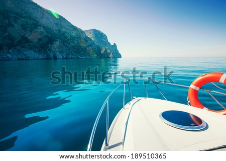Private boat floats near the mountains. Luxury Lifestyle. Traveling on a yacht. - stock photo