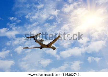 Private business jet airplane flying on blue sky, sun and clouds background - stock photo