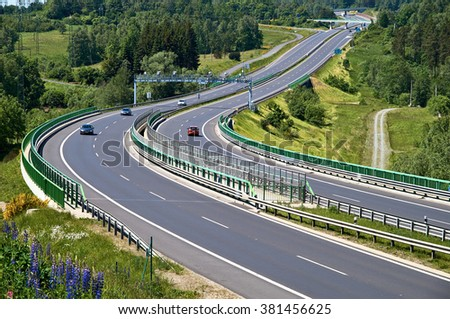 Private cars traveling on the asphalt highway with electronic toll gates in a wooded landscape. View from above. Sunny summer day. - stock photo