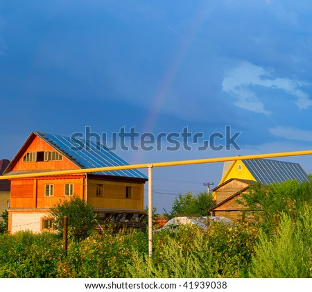 Private country houses against a summer landscape with rainbow. Shallow DOF
