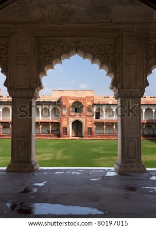 Private courtyard seen from under arches of Palace at Agra Fort in India. Green grounds, blue skies, beige arches frame red gate and white gallery.